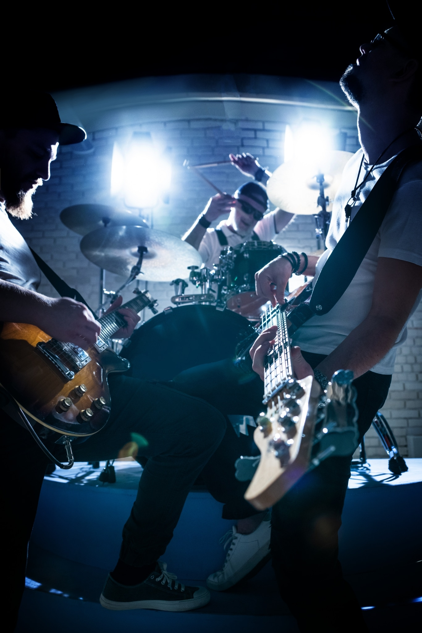 Two guitarists and a drummer play musical instruments