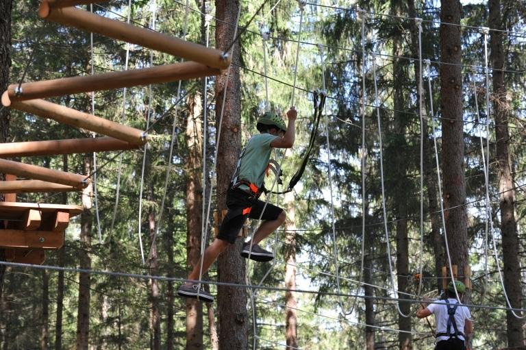 Ein Junge klettert im Hochseilgarten Oberwölz in der Steiermark. JUFA Hotels bieten erholsamen Familienurlaub und einen unvergesslichen Winter- und Wanderurlaub.