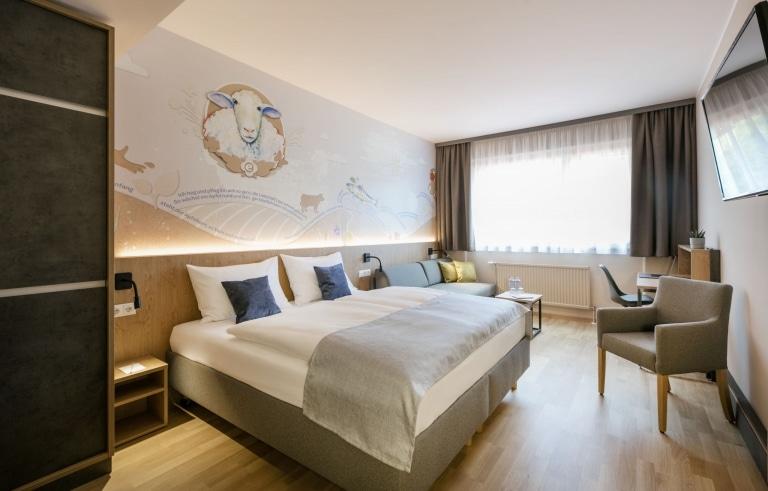 Sie sehen den Überblick eines Doppelzimmer im JUFA Hotel Weiz. Der Ort für kinderfreundlichen und erlebnisreichen Urlaub für die ganze Familie.