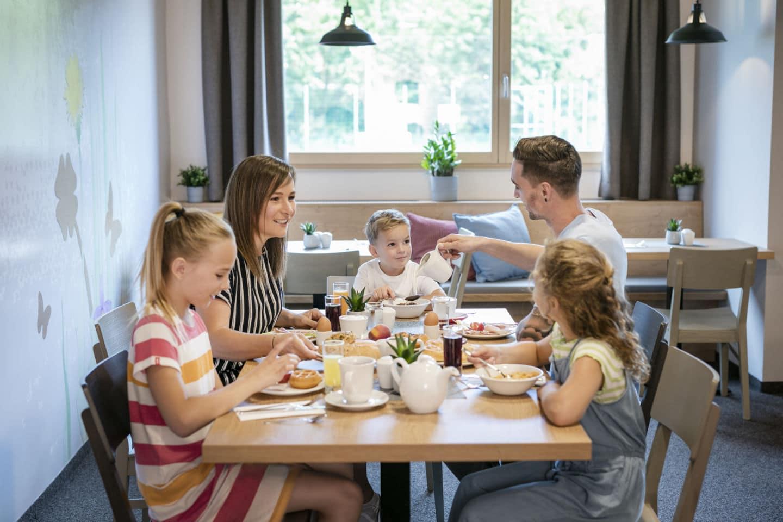 Sie sehen eine Familie beim frühstücken im JUFA Hotel Weiz