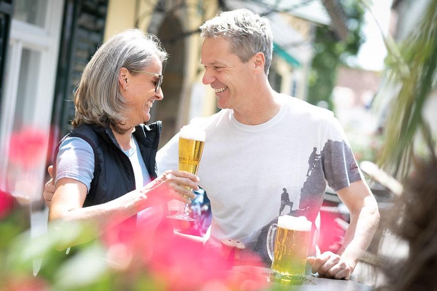 Sie sehen ein Pärchen beim genießen eines Biers vor dem Stadthotel zur goldenen Krone