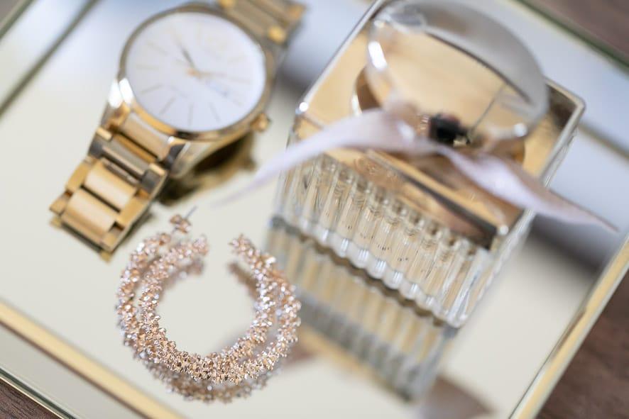 Sie sehen ein Bild einer goldenen Uhr, diamantenen Ohrringe und eines Parfums