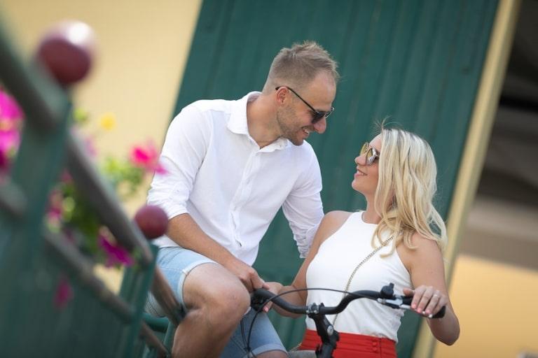Ein verliebtes Pärchen sitzt auf dem Fahrrad und lächelt sich an