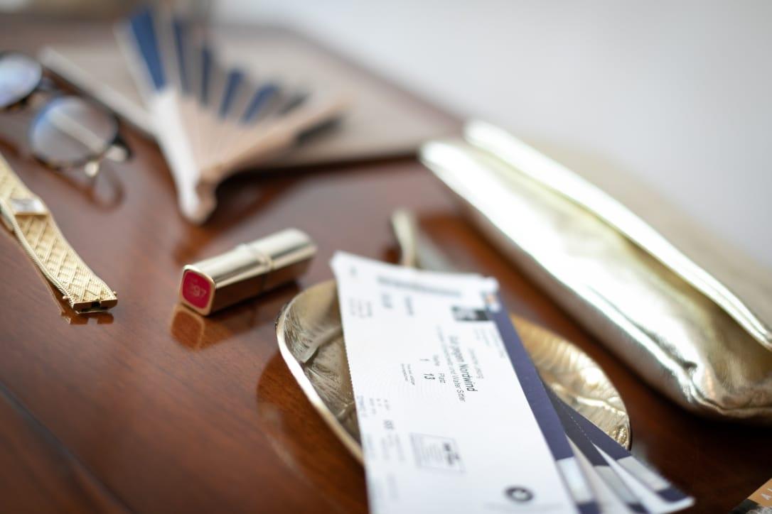 Sie sehen einen Tisch, auf welchem sich Konzertkarten, ein Fächer, eine Tasche und ein Lippenstift befinden