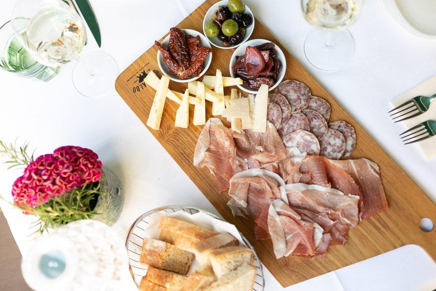 Ein Foto von einer kalten Vorspeisenplatte mit Prosciutto, Käse, Olive und ein Brotkörbchen