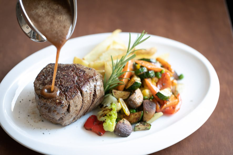 Sie sehen ein Steak, welches mit einer Sauce übergossen wird