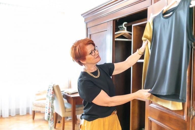 Eine Frau betrachtet Kleidungsstücke in grau und gold