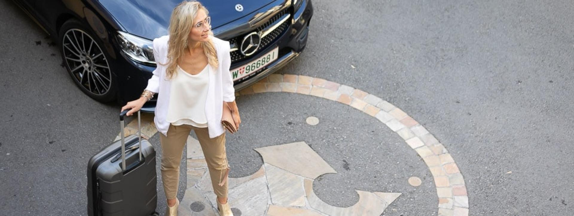 Eine junge Dame steht mit ihrem Koffer vor dem Stadthotel zur goldenen Krone