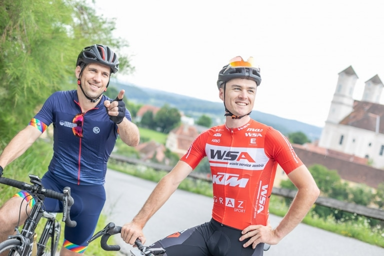 Zwei Männer mit Rädern stehe fahren auf den Landscha in Weiz. Im Hintergrund sieht man die Basilika am Weizberg.