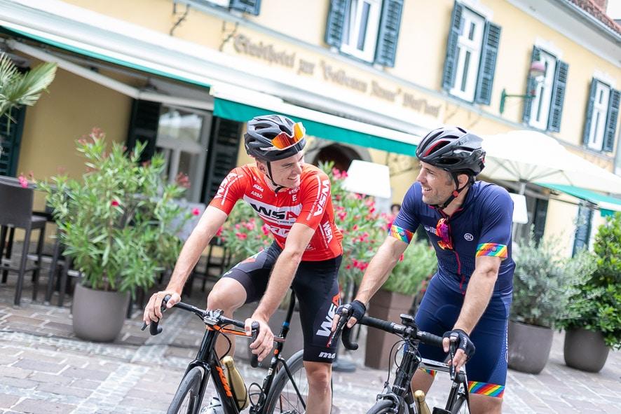 Zwei Männer mit Rädern stehen vor dem Stadthotel zur goldenen Krone