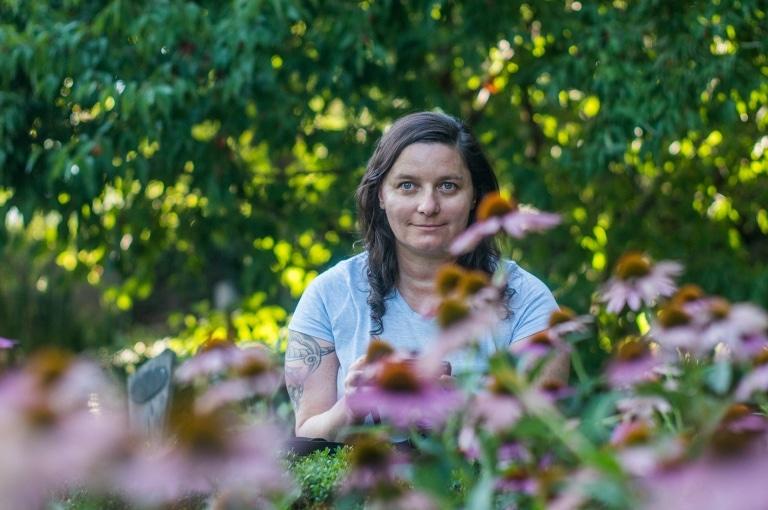 Alexandra Wagner sitz in mitten von Kräutern und Blumen